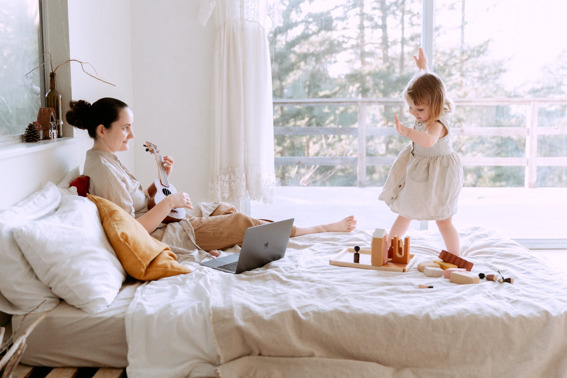 happy young woman playing ukulele for daughter at home